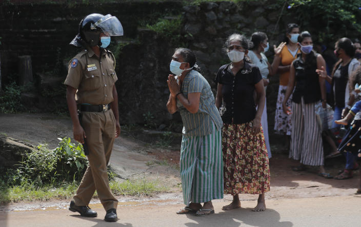 A family member of an inmate pleads to a policeman as she seeks information on the condition of her relative outside the Mahara prison complex following an overnight unrest in Mahara, outskirts of Colombo, Sri Lanka, Monday, Nov. 30, 2020. Sri Lankan officials say six inmates were killed and 35 others were injured when guards opened fire to control a riot at a prison on the outskirts of the capital. Two guards were critically injured. Pandemic-related unrest has been growing in Sri Lanka's overcrowded prisons. (AP Photo/Eranga Jayawardena)