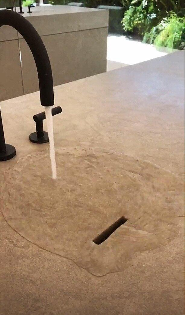 """Kim demonstrates that the custom designed (by Vervoordt and Kanye) counter has a slight slope, so that the water hits the surface and flows down into a slot at the edge that serves as a drain. """"You can put it on as high pressure as you want and no backsplash will come up,"""" she explains in the Instagram video."""