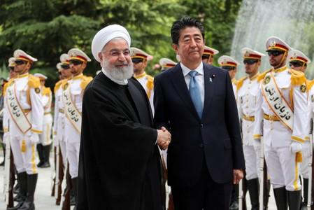 Iranian President Hassan Rouhani shakes hands with Japan's Prime Minister Shinzo Abe, during a welcome ceremony in Tehran