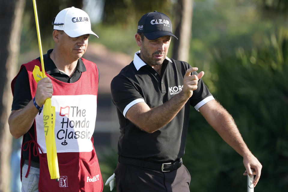 Charl Schwartzel of South Africa, right, talks to his caddie on the eighth hole during the first round of the Honda Classic golf tournament, Thursday, March 18, 2021, in Palm Beach Gardens, Fla. (AP Photo/Marta Lavandier)