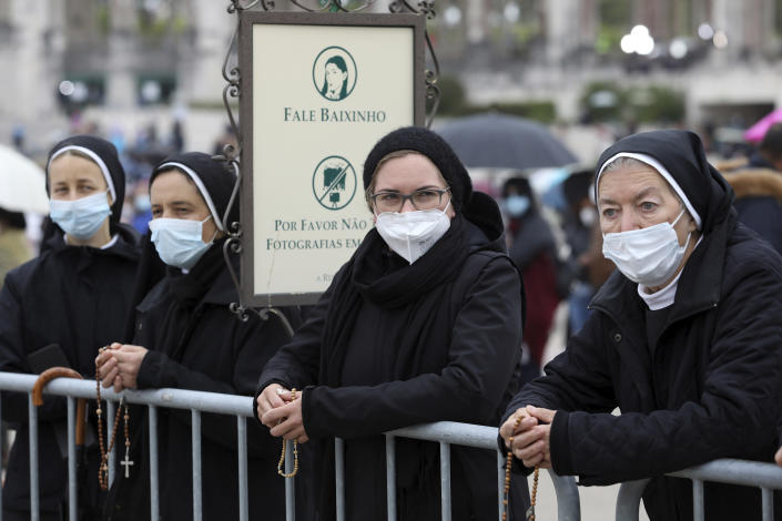 """A group of nuns wearing face masks hold rosaries while waiting for the start of the religious ceremonies at the Catholic shrine in Fatima, Portugal, Thursday, May 13, 2021. In view of the coronavirus pandemic, the shrine has limited to 7,500 the number of pilgrims that can be present during this year's May 12 and 13 celebrations usually attended by hundreds of thousands. The sign reads """" Speak low"""" and """" Please don't take group photos"""". (AP Photo/Ana Brigida)"""