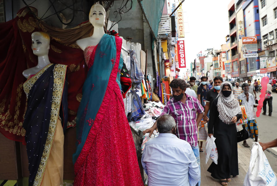A Sri Lankan Muslim woman, right in black attire, walks in a busy street of Colombo, Sri Lanka, Saturday, March 13, 2021. Sri Lanka on Saturday announced plans to ban the wearing of burqas and said it would close more than 1,000 Islamic schools known as madrassas, citing national security. ​(AP Photo/Eranga Jayawardena)