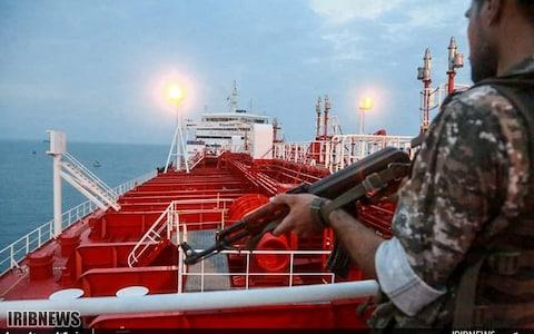 A member of the Iranian Revolutionary Guards onboard a tanker Stena Impero as it's anchored off the Iranian port city of Bandar Abbas - Credit: AFP