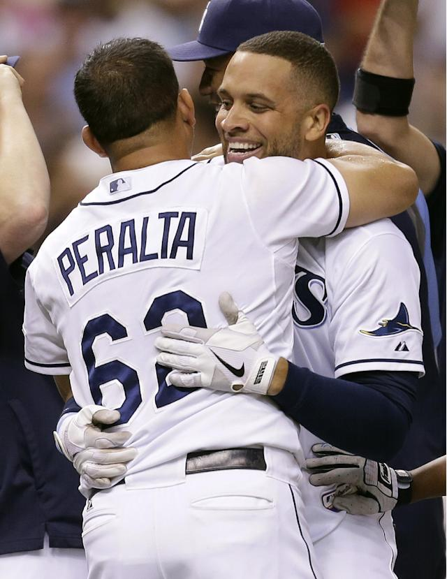 Tampa Bay Rays' James Loney, right, hugs relief pitcher Joel Peralta after Loney hit a ninth-inning, game-winning home run off Baltimore Orioles relief pitcher Tommy Hunter during a baseball game Monday, Sept. 23, 2013, in St. Petersburg, Fla. The Rays won 5-4. (AP Photo/Chris O'Meara)