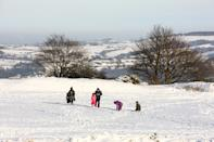 HUDDERSFIELD, UNITED KINGDOM - 2021/01/15: A family play in the snow at Castle Hill in Huddersfield. Many parts of West Yorkshire are still covered with snow following heavy snowfall the previous day, which caused widespread disruption to travel. (Photo by Adam Vaughan/SOPA Images/LightRocket via Getty Images)