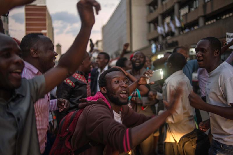Harare residents celebrate in front of the parliament.