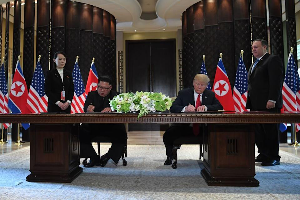 Trump and Kim Jong Un sign documents as US Secretary of State Mike Pompeo and the North Korean leader's sister Kim Yo Jong look on. Source: Getty