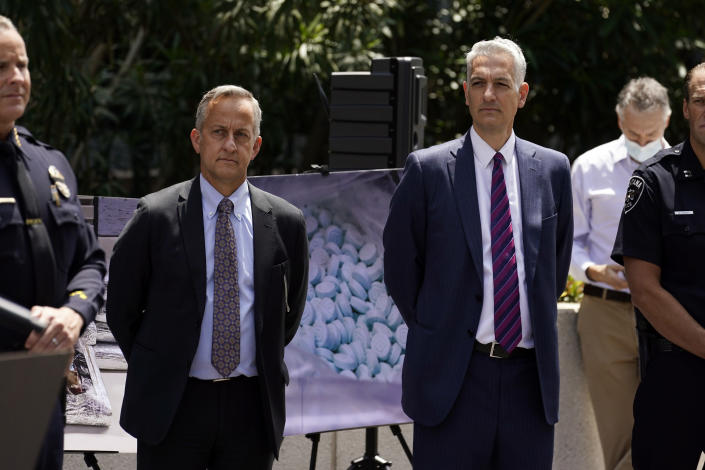 Agents stand in front of images of illegal drugs outside the Edward R. Roybal Federal Building, Thursday, May 13, 2021, in Los Angeles. Federal authorities say they have arrested at least 10 suspected drug dealers accused of selling fentanyl and other opioids that led to overdose deaths. (AP Photo/Marcio Jose Sanchez)