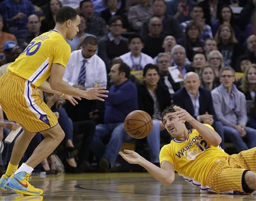 Golden State Warriors' Andrew Bogut, right, passes from the floor to Stephen Curry during the first half of an NBA basketball game against the Houston Rockets Friday, March 8, 2013, in Oakland, Calif. (AP Photo/Ben Margot)