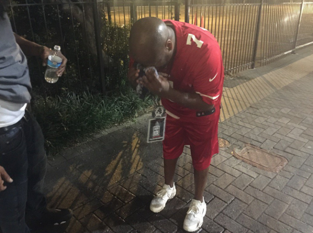 Shawn Richardson wipes away a spray allegedly used by police to break up a protest. (Yahoo Sports)