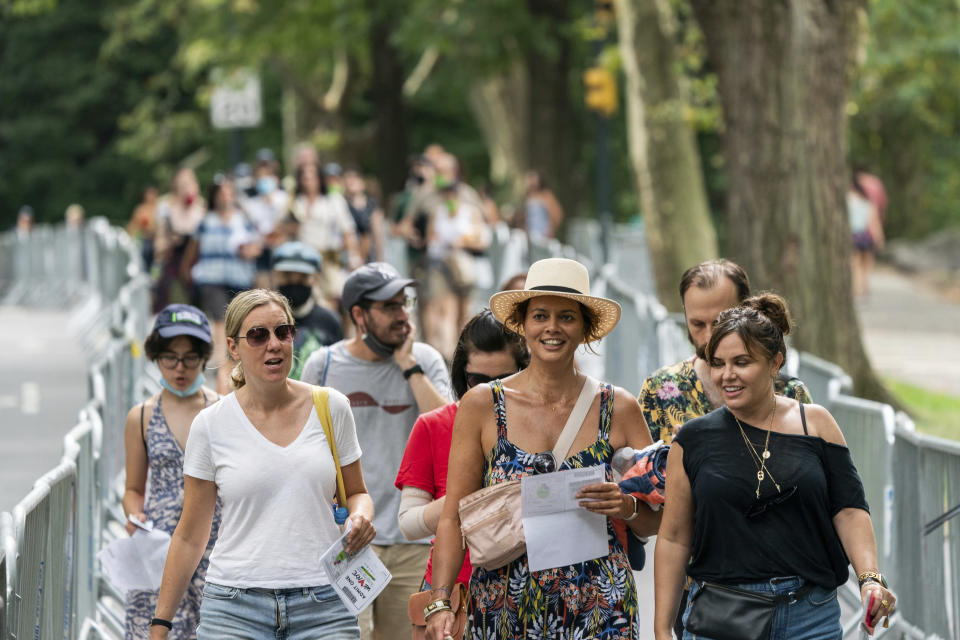 """People arrive before the """"We Love NYC: The Homecoming Concert"""" in New York's Central Park, Saturday, Aug. 21, 2021. We Love NYC, The Homecoming Concert celebrates its recovery from the coronavirus pandemic despite surging cases and hospitalizations due to the delta variant. (AP Photo/Jeenah Moon)"""