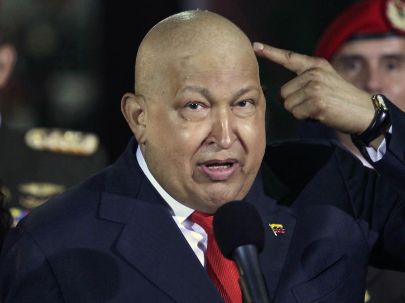 FILE - In this Oct. 11, 2011, file photo, Venezuela's President Hugo Chavez points at his head to show that his hair has started to grow back after his last round of chemotherapy at Miraflores presidential palace in Caracas, Venezuela. Venezuela's Communication and Information Minister Ernesto Villegas on Monday, March 4, 2013, reported that President Hugo Chavez's health has deteriorated and remains delicate. Villegas also announced in the national TV broadcaster VTV that the president is undergoing chemotherapy with high impact. (AP Photo/Ariana Cubillos, file)