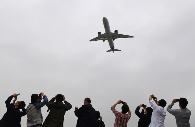 Spectators take photos as they watch the Comac C919, China's first large passenger jet, coming in for a landing on its maiden flight at Shanghai's Pudong airport