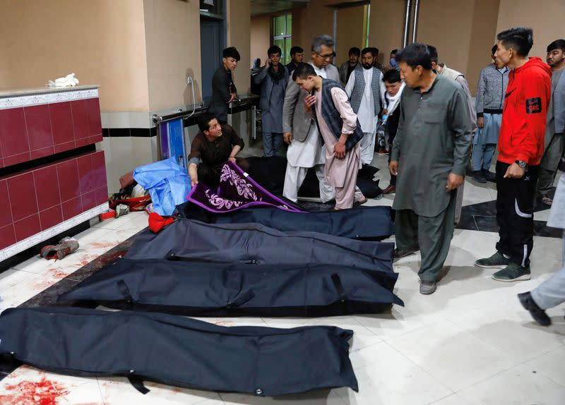 Afghan men look for their relatives at a hospital after a suicide bombing in Kabul