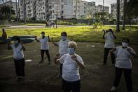 Wearing face masks amid the new coronavirus pandemic, people practice Tai Chi in a park in Havana, Cuba, Wednesday, Oct. 28, 2020. Few countries in Latin America have seen as dramatic a change in U.S. relations during the Trump administration or have as much at stake in who wins the Nov. 3rd presidential election. (AP Photo/Ramon Espinosa)
