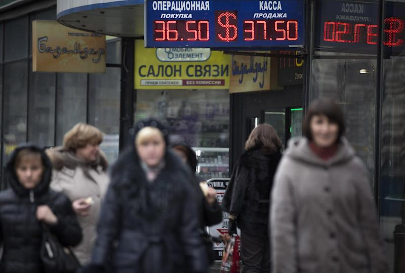 People walk past a currency exchange office in downtown Moscow, Russia, Monday, March 3, 2014. Russia's markets have dropped about 10 percent and its currency has fallen to its lowest point ever against the dollar and the euro because of the crisis in neighboring Ukraine. Russia intervened over the weekend to take control of Crimea, a Ukrainian peninsula with strategic importance, and the new government in Kiev fears a wider invasion. (AP Photo/Alexander Zemlianichenko)