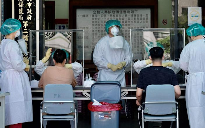 Medical staffers collect samples from local residents during a coronavirus testing drive at the Xindian District in New Taipei City - Sam Yeh / AFP