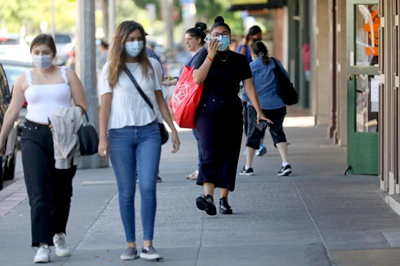 ORANGE, CA - JUNE 18: People shopping and strolling at the Orange Circle on Thursday, June 18, 2020 in Orange, CA. Gov. Gavin Newsom on Thursday ordered all Californians to wear face coverings while in public or high-risk settings due to coronavirus. Orange County recently did not require face mask to be worn. (Gary Coronado / Los Angeles Times)