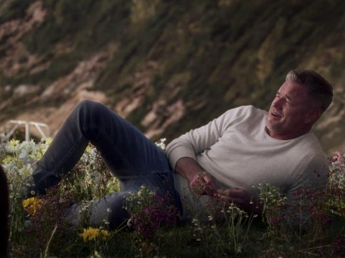 Mark sitting in the flowers on a beach wearing a white sweater and jeans on Greys Anatomy
