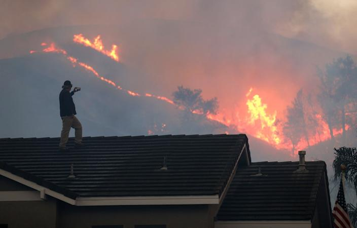 Herman Termeer watches the Blue Ridge fire burn Tuesday inside Chino Hills State Park from the roof of his home.