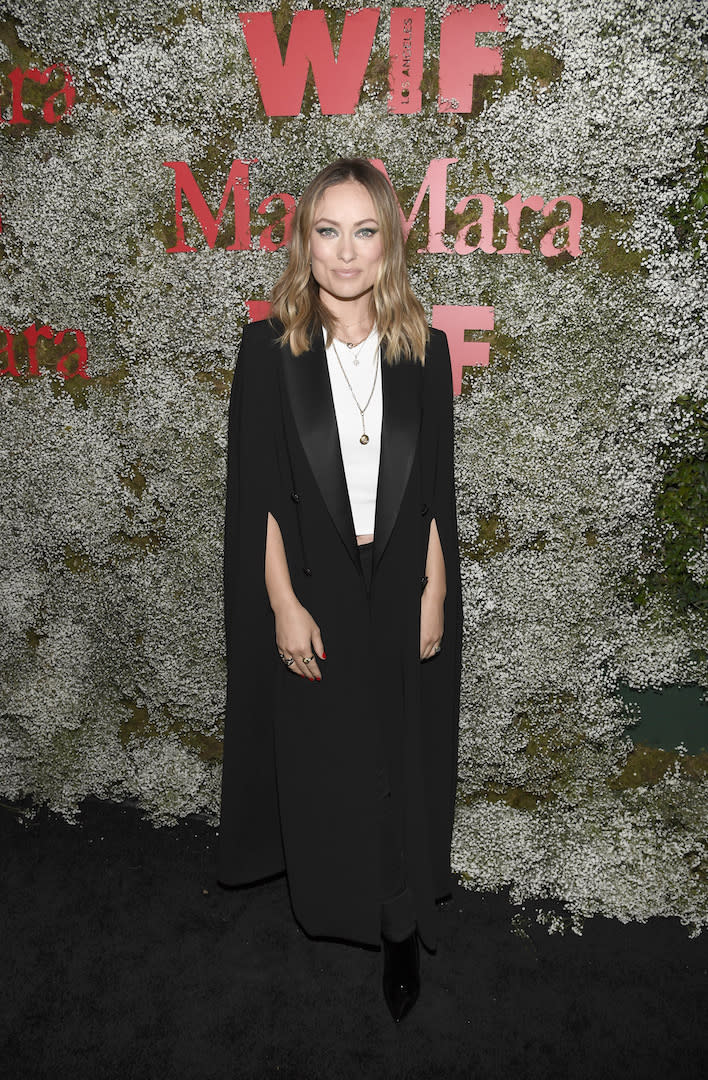 On June 11, Olivia Wilde convinced us that we need to shop for a caped coat asap in this seriously chic Max Mara number. <em>[Photo: Getty]</em>