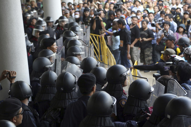 Thai anti-government protesters, right, confront with riot policemen after a brief scuffle in an attempt to disrupt the election registration at a sport gymnasium in Bangkok, Thailand Wednesday, Dec. 25, 2013. Thai Prime Minister Yingluck Shinawatra on Wednesday proposed the formation of a national reform council tasked with finding solutions to the political turmoil that is splitting the country and paralyzing governance. (AP Photo/Apichart Weerawong)