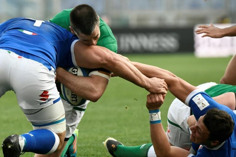 Italy's Marco Lazzaroni (L) and fly-half Paolo Garbisi (R) tackle Ireland captain Johnny Sexton in Rome.