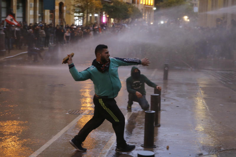 Anti-government protesters clash with the riot police during ongoing protests in Beirut, Lebanon, Wednesday, Jan. 22, 2020.  Lebanon's new government held its first meeting Wednesday, a day after it was formed following a three-month political vacuum, with the prime minister saying his Cabinet will adopt financial and economic methods different than those of previous governments. (AP Photo/Bilal Hussein)