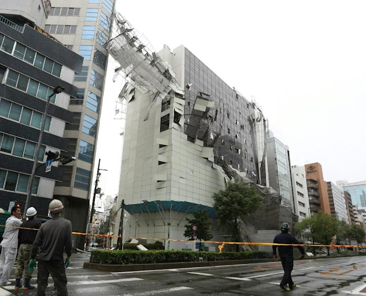 Scaffolding is torn off a building in Osaka raked by the high winds