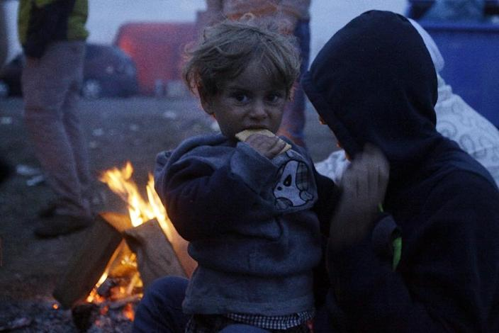 A child eats a biscuit as migrants sit around a fire near Roszke on the Hungarian-Serbian border on September 9, 2015 (AFP Photo/Peter Kohalmi)