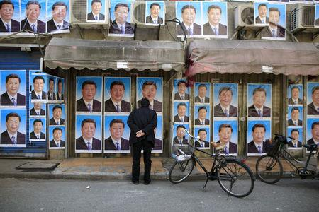 FILE PHOTO: A man looks at a building covered in hundreds of posters of Chinese President Xi Jinping in Shanghai, China, March 26, 2016. REUTERS/Aly Song/File Photo