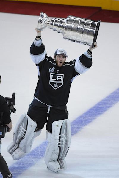 Los Angeles Kings goalie Jonathan Quick carries the Stanley Cup after the Kings beat the New York Rangers in Game 5 of the NHL Stanley Cup Final series Friday, June 13, 2014, in Los Angeles. The Kings won, 3-2. (AP Photo/Mark J. Terrill)