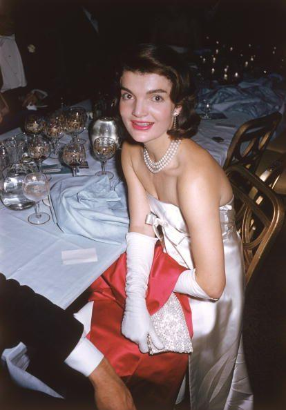 "<p>Jackie Kennedy attends an ""April in Paris"" ball, sporting pearls, gloves, and a strapless dress.</p>"