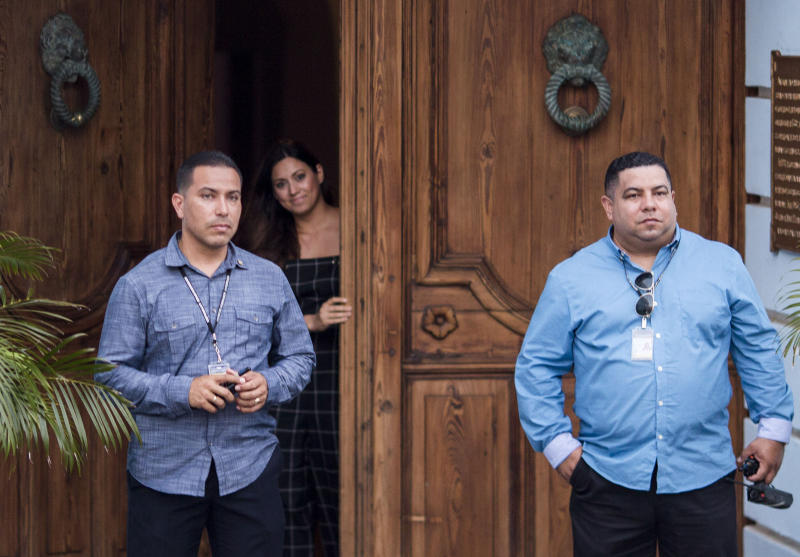 Puerto Rico's first lady Beatriz Rossello opens La Fortaleza Main Gate to let her dogs out, as two security men stand guard at La Fortaleza, the Governor's Mansion in San Juan, Puerto Rico, Wednesday, July 24, 2019. Protesters are demanding that Gov. Ricardo Rossello step down for his involvement in a private chat in which he used profanities to describe an ex-New York City councilwoman and a federal control board overseeing the island's finance. (AP Photo/Dennis M. Rivera Pichardo)