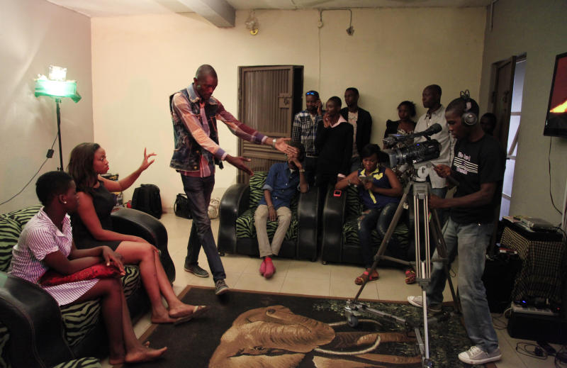 """In this photo taken Wednesday, Sept, 18. 2013, Nollywood actors perform a scene in Lagos, Nigeria. A 15-second drum roll and the title of the film, """"Deceptive Heart,"""" comes crashing onto the screen in a groovy 1970s font. Less than 10 minutes into the Nollywood movie, the heart of plot is revealed: A woman has two boyfriends and doesn't know what to do. The story moves as quickly as the film appears to have been shot. Some scenes are shaky, with cameras clearly in need of a tripod, and musical montages are often filled with pans of the same building. Most Nollywood movies are made in less than 10 days and cost about $25,000. (AP Photo/ Sunday Alamba)"""