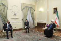 In this photo released by the official website of the office of the Iranian Presidency, Iranian President Hassan Rouhani, right, and Russian Foreign Minister Sergey Lavrov, left, wear face masks to curb the spread of COVID-19 during their talks in Tehran, Iran, Tuesday, April 13, 2021. (Iranian Presidency Office via AP)