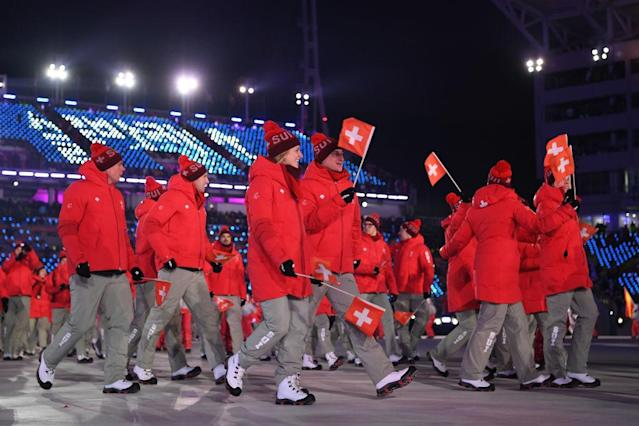 <p>Swiss athletes take part in the Team Parade wearing crimson winter jackets, gray pants, and pom-pom beanies during the opening ceremony of the 2018 PyeongChang Games. (Photo: Quinn Rooney/Getty Images) </p>