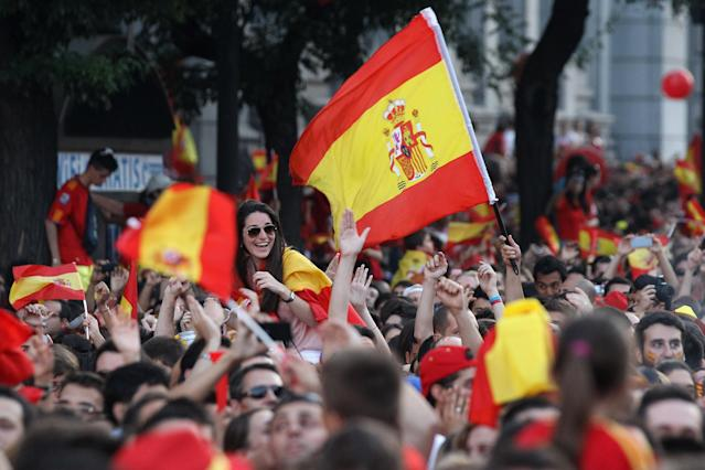 MADRID, SPAIN - JULY 02: Supporters of Spain's national football team fly the national flag as they congratulate their team's players on their return to Madrid following their victory in Euro 2012 football championships on July 2, 2012 in Madrid, Spain. Spain beat Italy 4-0 in the UEFA EURO 2012 final match in Kiev, Ukraine, on July 1, 2012. (Photo by Oli Scarff/Getty Images)