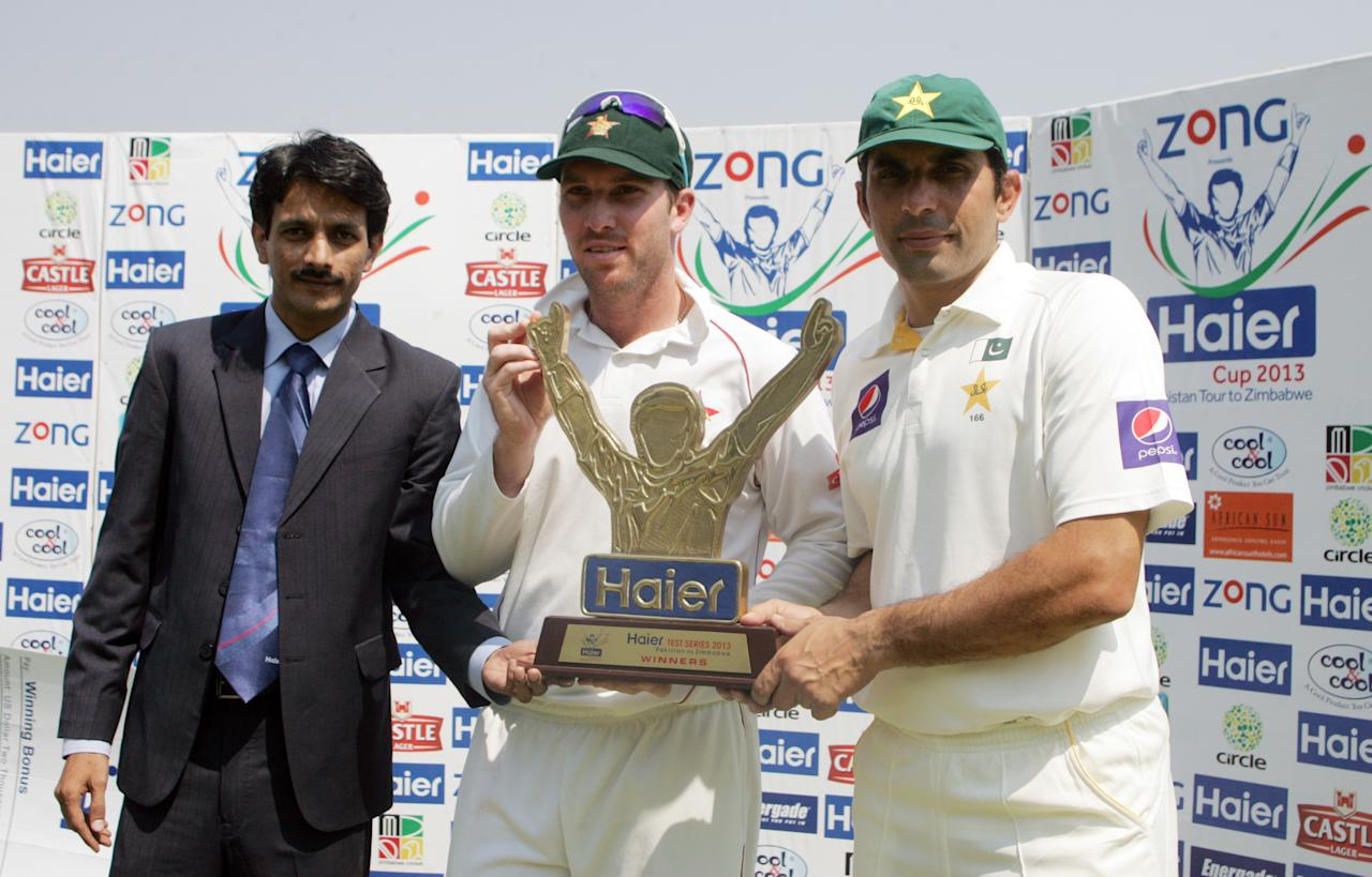 Zimbabwe captain Brendan Taylor (L) and Pakistan captain Misbah Ul Haq (R) share the series trophy on September 14, 2013 during the fifth day of the second Test against Pakistan at the Harare Sports Club.                              AFP PHOTO / JEKESAI NJIKIZANA        (Photo credit should read JEKESAI NJIKIZANA/AFP/Getty Images)
