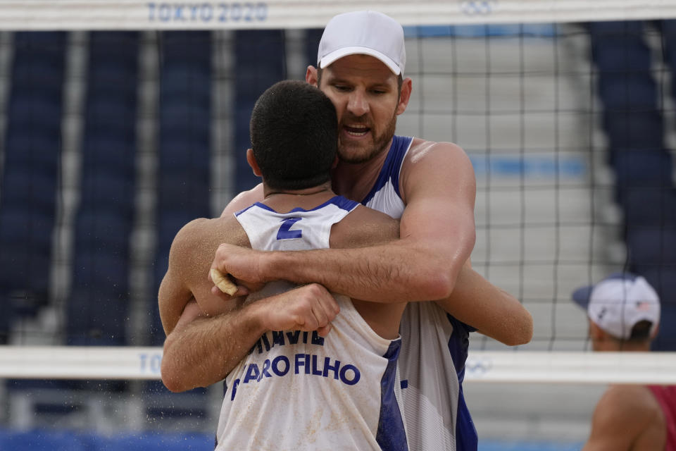 Alison Cerutti, right, of Brazil, hugs teammate Alvaro Morais Filho during a men's beach volleyball match against the United States at the 2020 Summer Olympics, Tuesday, July 27, 2021, in Tokyo, Japan. (AP Photo/Petros Giannakouris)