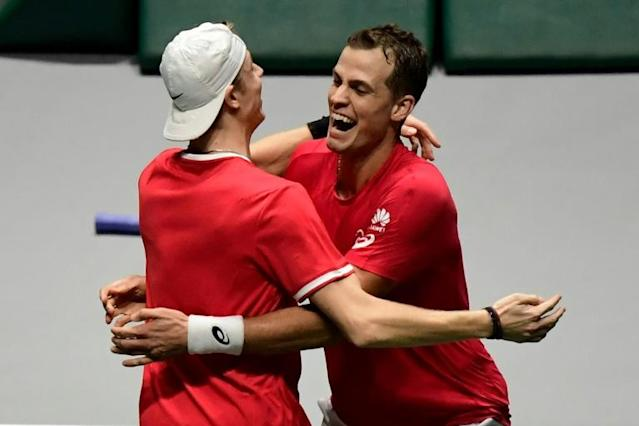 Canada's Vasek Pospisil (right) and Denis Shapovalov celebrate after winning the crucial doubles rubber against Australia. (AFP Photo/JAVIER SORIANO)