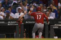 Cincinnati Reds' Kyle Farmer (17) celebrates with manager David Bell, left, at the dugout after hitting a solo home run during the fourth inning of a baseball game against the Chicago Cubs, Monday, July 26, 2021, in Chicago. (AP Photo/Paul Beaty)
