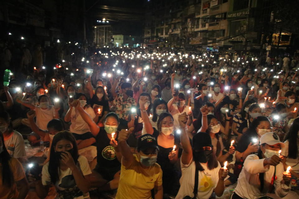 People raise their hands with clenched fists while others hold up mobile phones with LED lights on, during a candlelight night rally in Yangon, Myanmar Saturday, March 13, 2021. Security forces in Myanmar on Saturday again met protests against last month's military takeover with lethal force, killing at least four people by shooting live ammunition at demonstrators. (AP Photo)