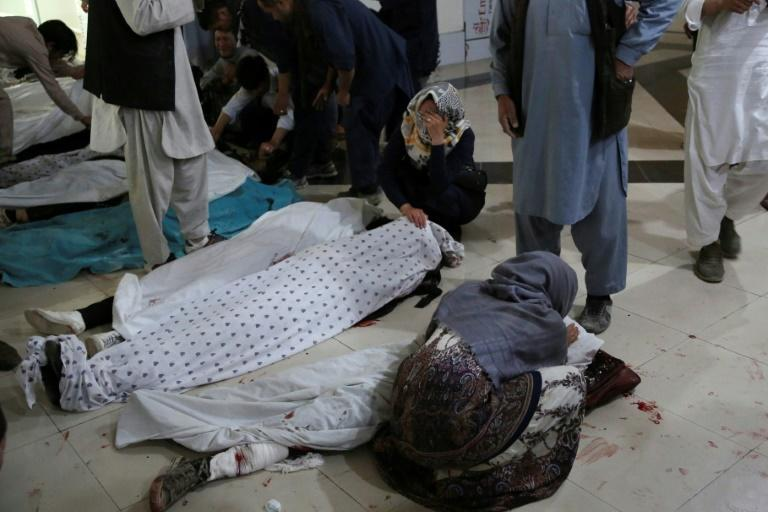 Family members and relatives mourn inside a hospital while sitting next to the bodies of victims who died in a blast outside a school in west Kabul