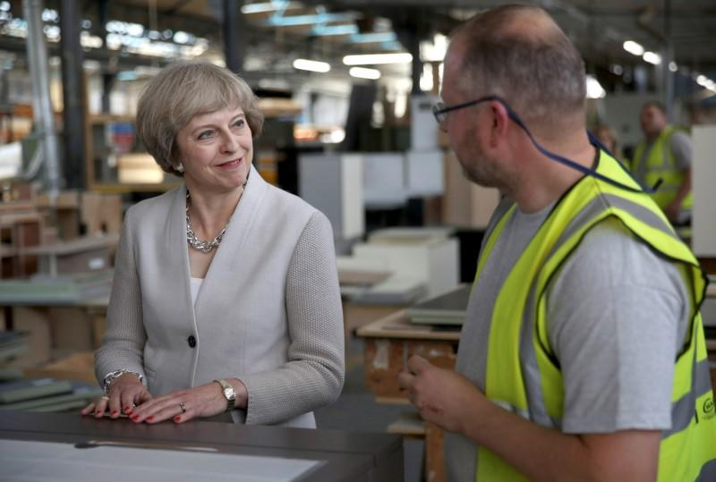 Britain's Prime Minister Theresa May speaks with a worker as she visits a joinery factory in London
