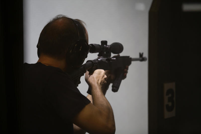 """AURORA, CO - JULY 22:  A  member of Firing-Line prepares fires his weapon at the gun range July 22, 2012 in Aurora, Colorado. Firing-Line is located not far from where suspect gunman James Eagan Holmes, 24, is accused of killing 12 people at a screening of the new """"Batman"""" film last Friday. (Photo by Joshua Lott/Getty Images)"""
