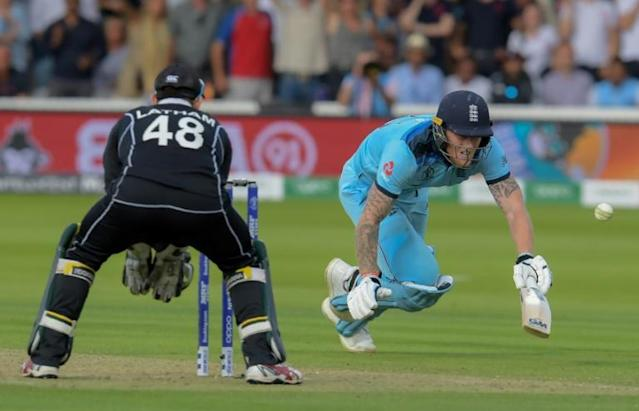 England's Ben Stokes dives to make his ground and the ball deflects to the boundary (AFP Photo/Dibyangshu Sarkar)