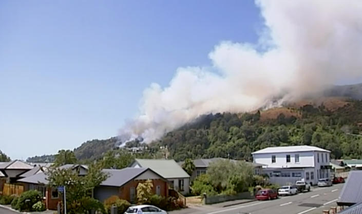 In this image made from video, smoke rises from a wildfire coming over the ridge behind a residential area, Friday, Feb. 8, 2019, in Wakefield, New Zealand. About 700 residents were evacuated from a New Zealand town on Friday as a forest fire threatened the area. (Newshub via AP)