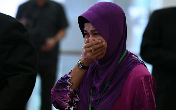 Sarah Nor, the mother of Norliakmar Hamid, a passenger on missing Malaysia Airlines flight MH370, cries as she arrives for the final investigation report - AFP
