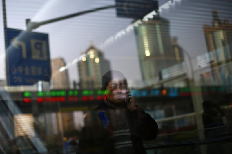 A man walks out of a subway station as he talk on the phone at the financial district of Pudong in Shanghai